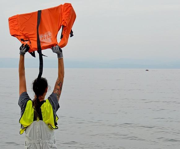 A volunteer signals to a refugee boat near Skala Syknaminia.