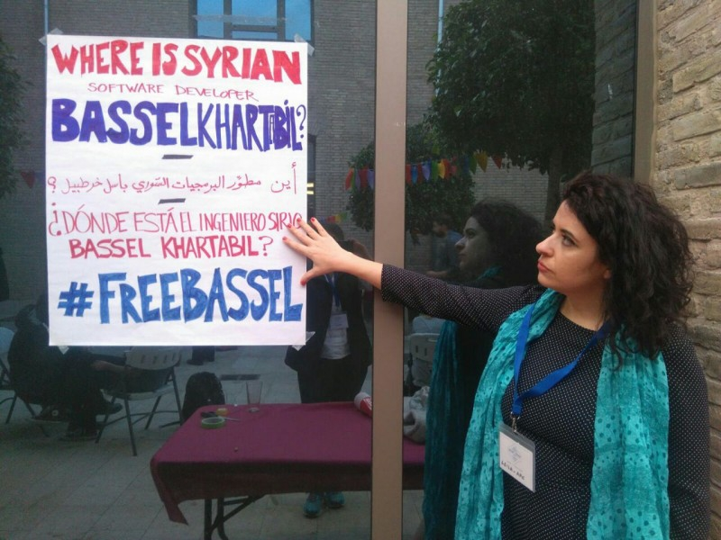 Rego points to a poster appealing for the freedom of Syrian software developer Bassel Khartabil.