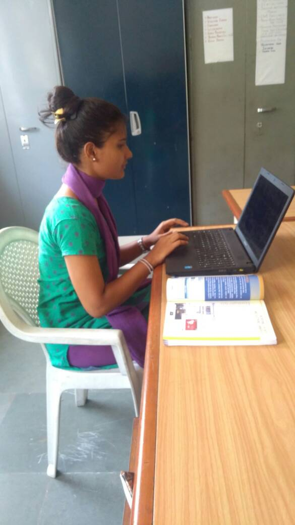 A young girl sits at a computer in India.