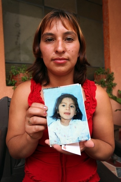 Loyda Rodríguez holding a photograph that shows her daughter Anyelí.