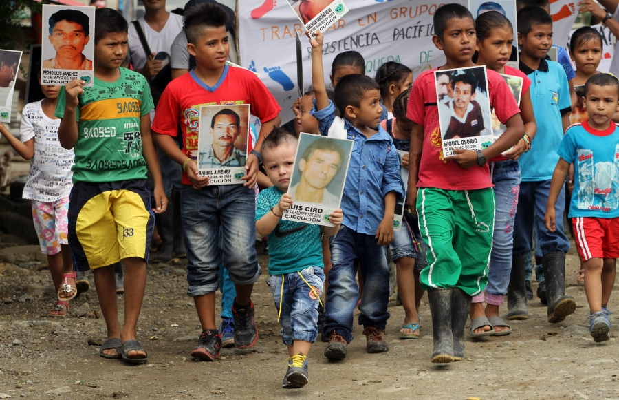 Kids carrying signs showing faces of massacred