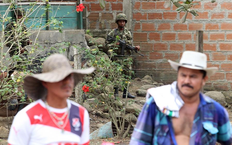 Soldier looks on as San José de Apartadó Peace Community members commemorate 19 years of peaceful resistance.