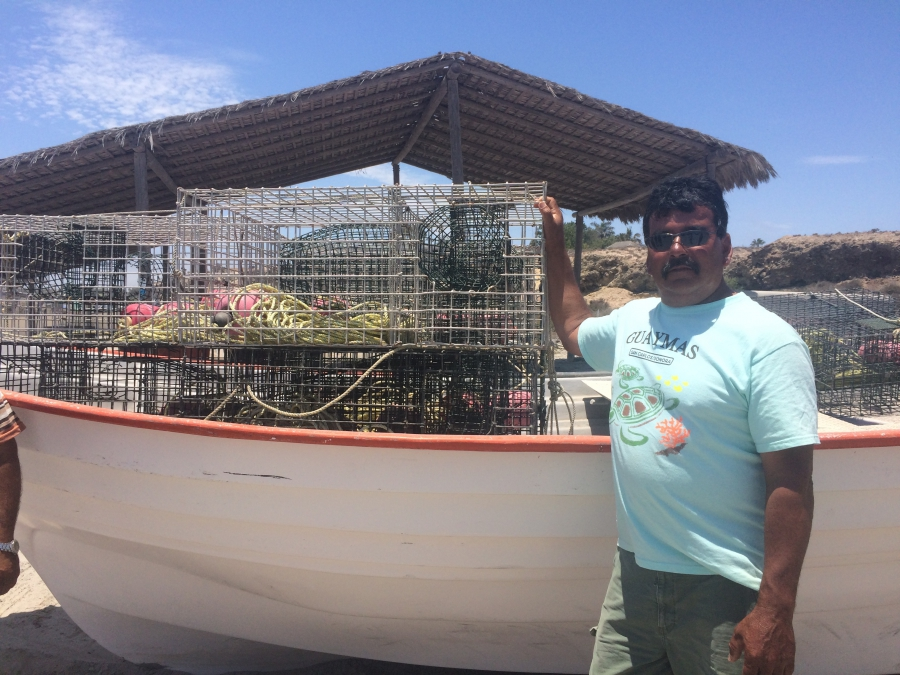 Fisherman Juan Luis Aguilar stands by his boat full of lobster traps and nets on the beach at San Juanico. He and other members of the local fishing cooperative fear the proposed undersea phosphate mine will put them out of business.