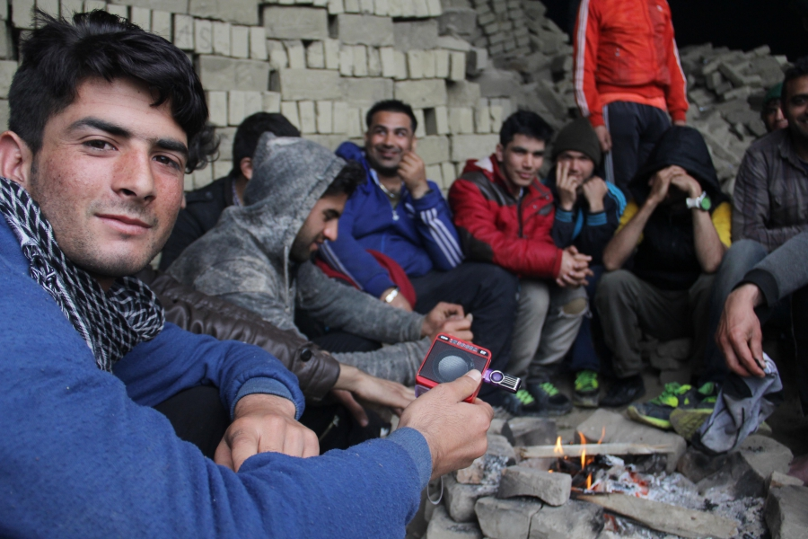 An Afghani migrant plays music from a memory stick on a small speaker where he is camping in an abandoned brick factory near the Serbian-Hungarian border.