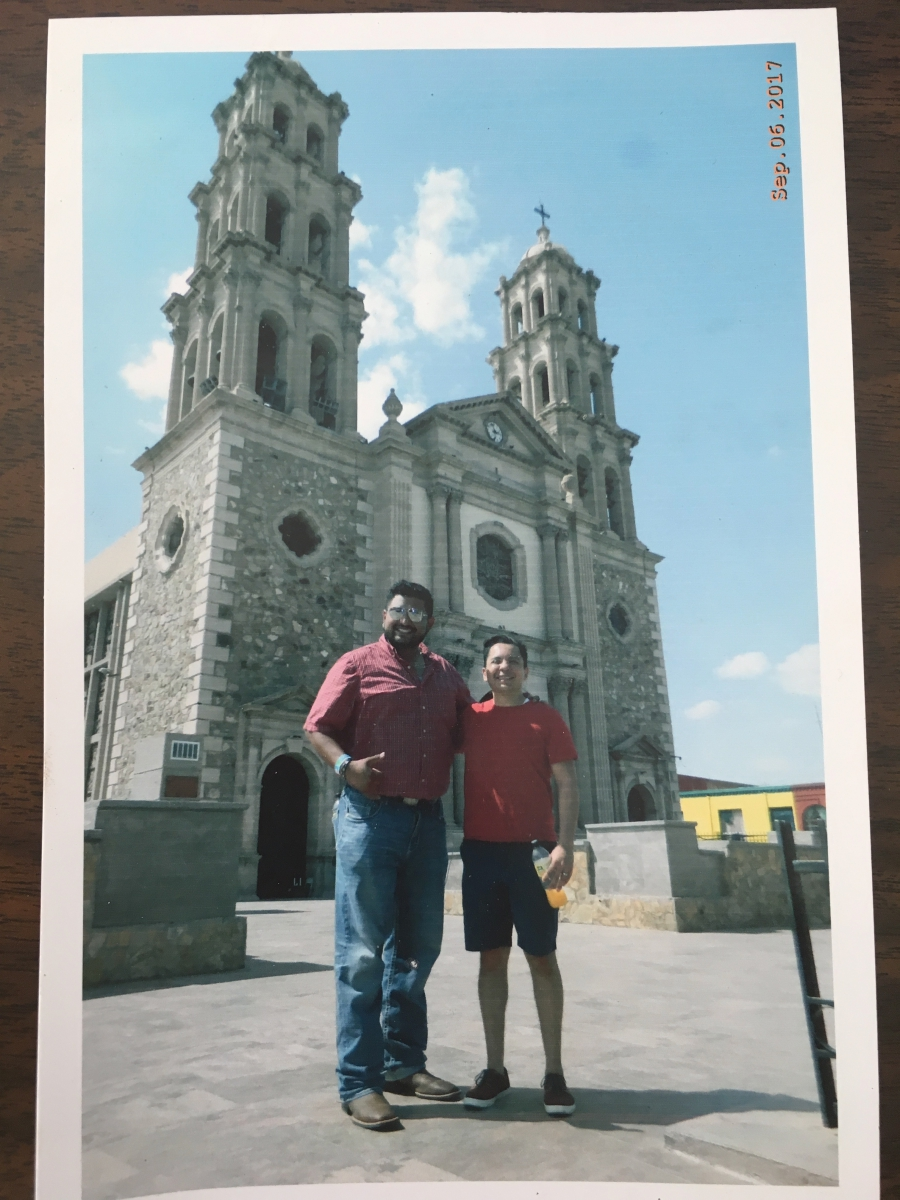 Two men pose in front of elaborate cathedral