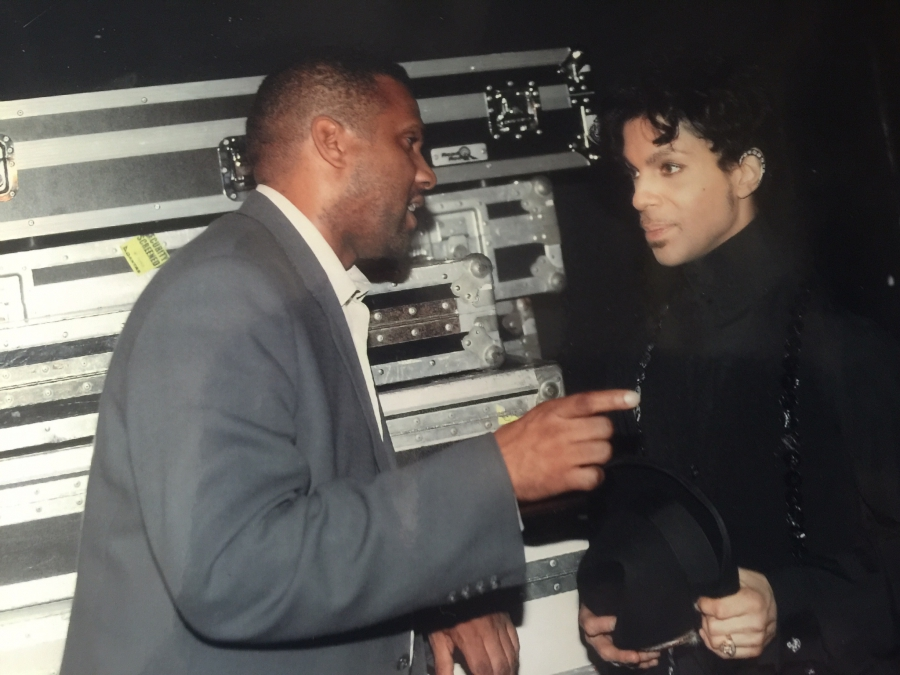 Tavis gestures to Prince in front of large carrying cases for the tour