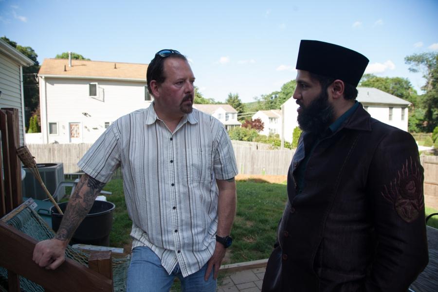 Two men standing outdoors talking