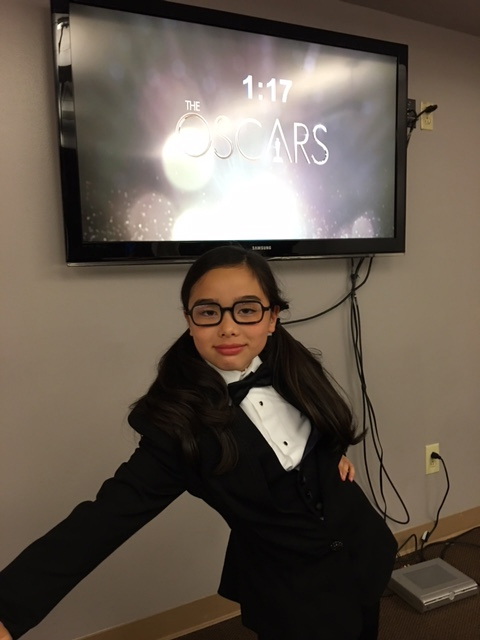 Estie Kung looks excited, with a screen of a countdown to her appearance on the Oscars behind her.