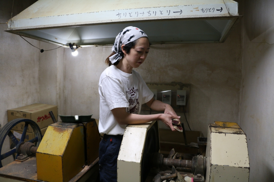Akiko Kawanami shaves katsuibushi flakes in her family's shop. She grew up in the building above it.