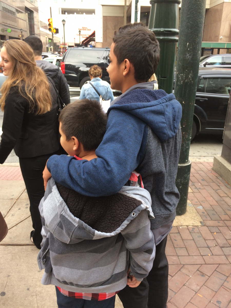 Two young boys face away from camera, on sidewalk