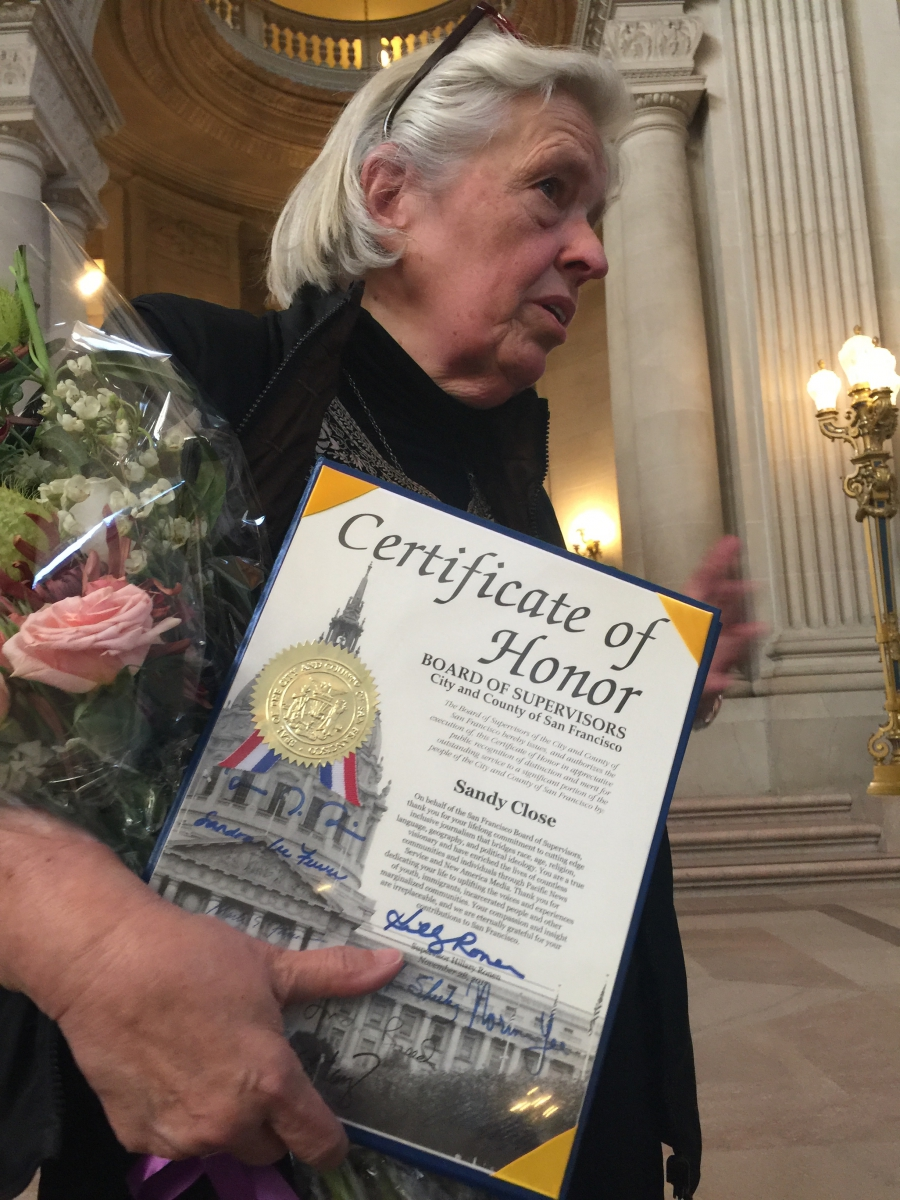 Woman stands with certificate, flowers behind