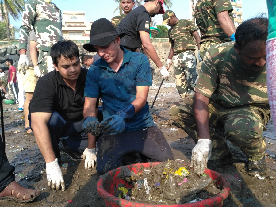 Afroz Shah shows another volunteer what he does with the trash he finds on his beach