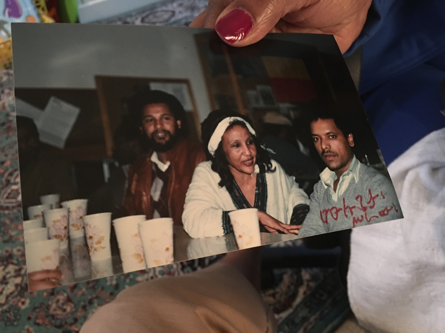 Endeyu Kendie holds a picture of one of the Ethiopian community's parties in the 1980s, with Mulugeta Seraw pictured at right.