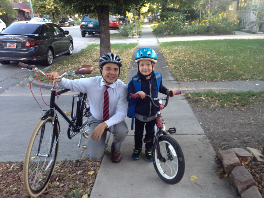 Man wearing helmet and tie kneels on sidewalk next to boy on bike, also wearing helmet