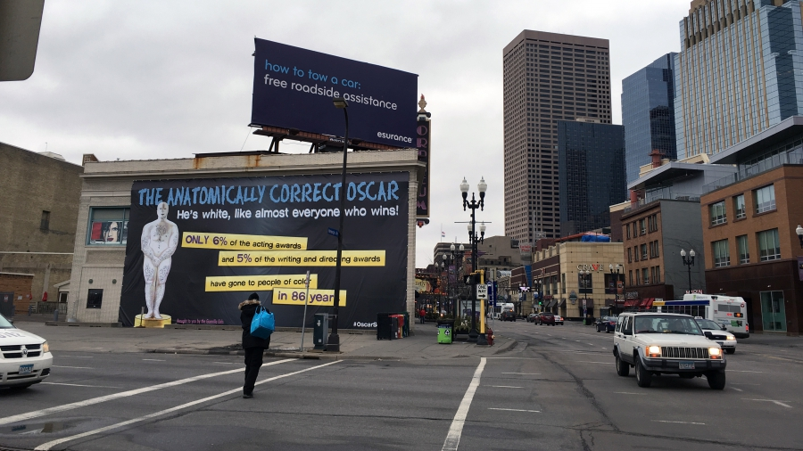A view of a Guerrilla Girls poster in Minneapolis from across the street. The poster shows a cartoon version of the Oscar as a white man and covers one side of a midrise building downtown.