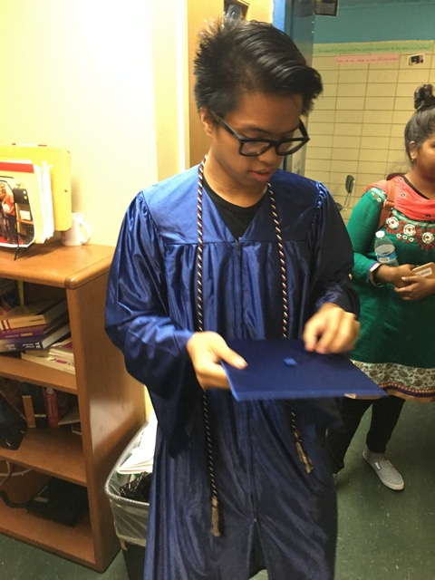 Young man in blue graduation gown, holding cap