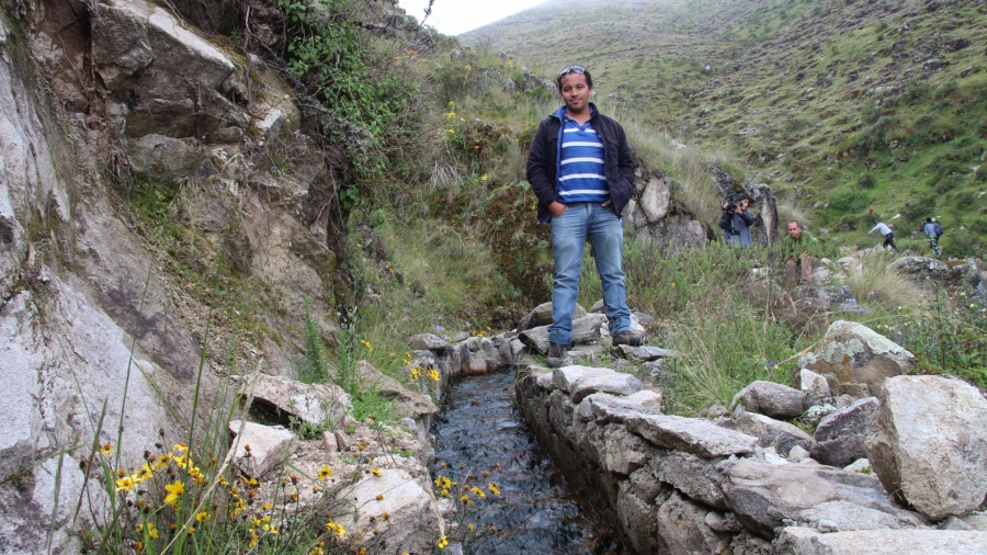 Oscar Angulo, a hydrologist for the NGO Condesan, stands by a restored stretch of canal near Huamantanga. well-manicured canal. When he first came to the town in 2012, the canals were littel more than piles of rubble, largely abandoned as young people lef