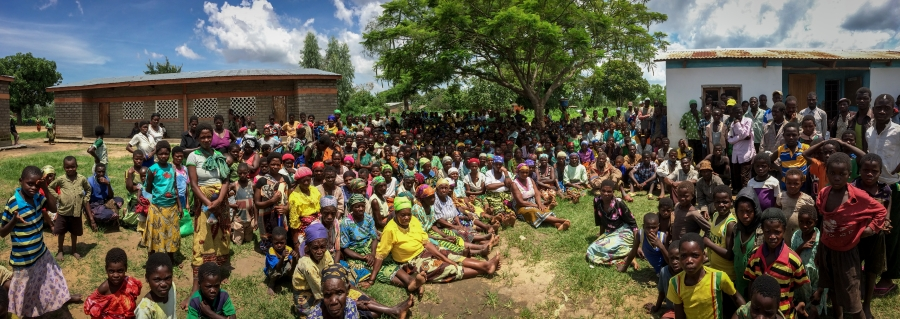 Some of the 2,000 flood victims now sheltered at the Milala Primary School in Makawa gather on the gather outside two of the school's buildings. Malaria and malnutrition are starting to take hold in the isolated camp.