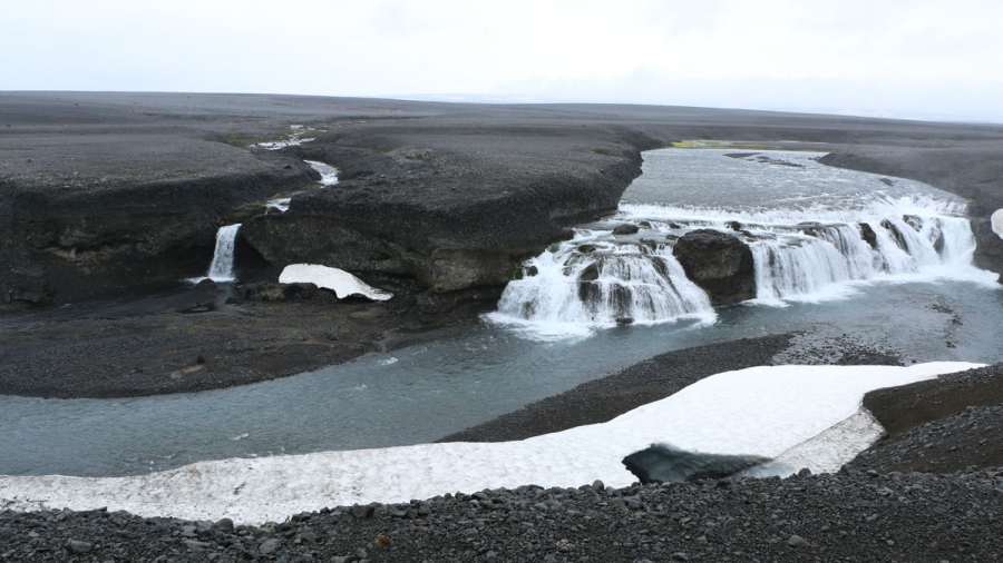 A waterfall cascades in an otherwise desolate volcanic landscape.