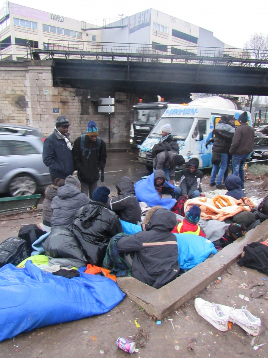 A group of Sudanese migrants huddles on top a subway grate in northern Paris to keep warm.