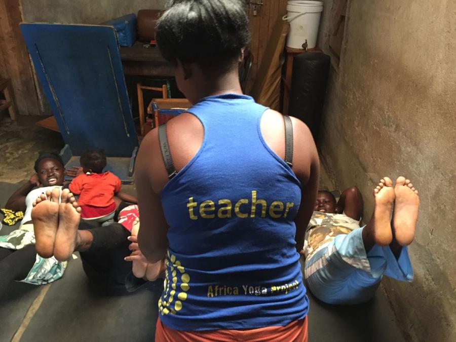 Joyce Wanjiku assists first time yoga students in the Nairobi slum of Kariobangi.
