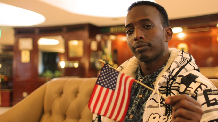 """""""Mr. America"""" shows off his adopted country's flag."""