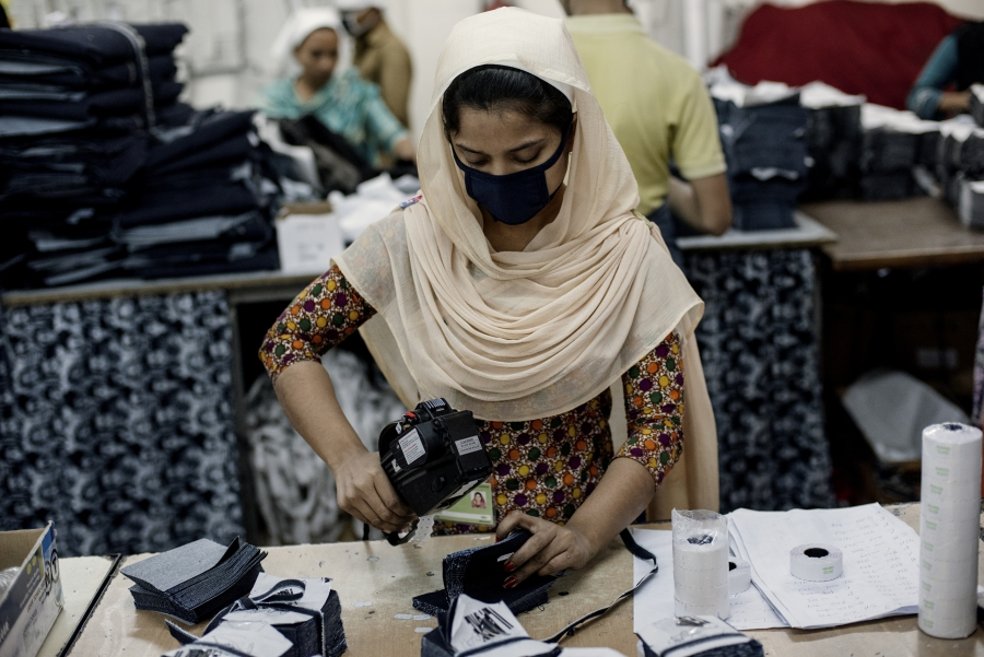 Garment factory worker making denim jeans.