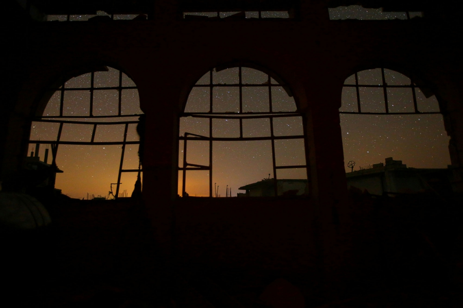 The night sky is seen through damaged windows in the rebel-controlled town of Binnish in Idlib province.
