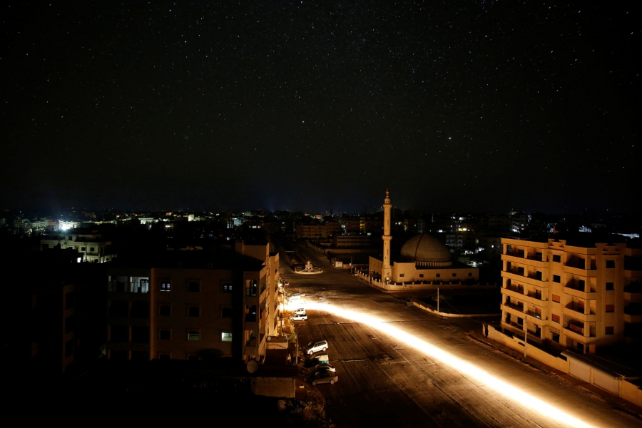 A vehicle drives past a mosque at night in Idlib, Syria.