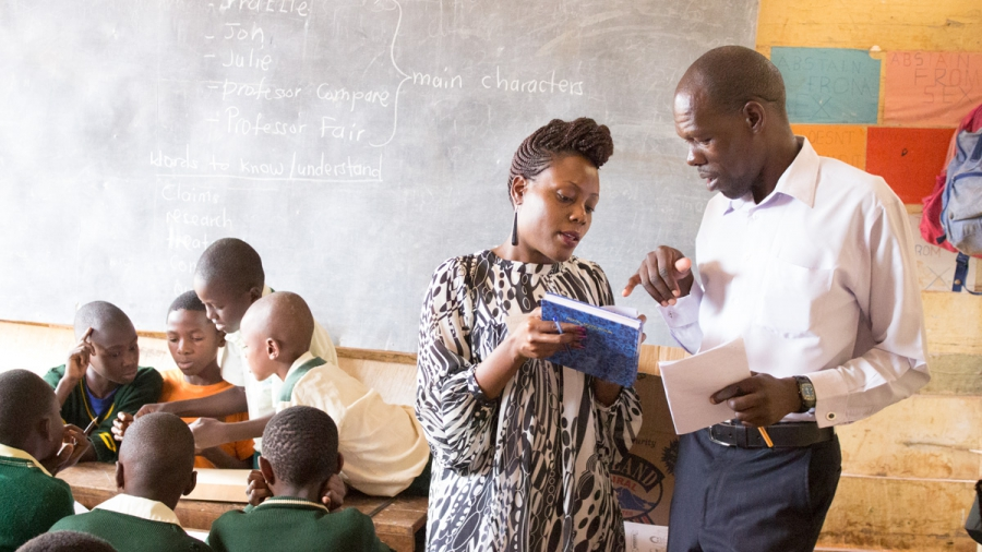 A school administrator (right) and Ugandan researcher Allen Nsangi discuss the project during a pilot lesson. Nsangi was a primary investigator in the development and evaluation of the Informed Health Choices primary school intervention.