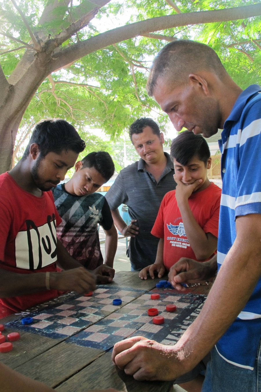 Many Central American migrants pass the days playing competitive games of checkers at the local migrant shelter in Ixtepec, Mexico. The city, as well as the surrounding region, was devastated by last September's earthquakes.