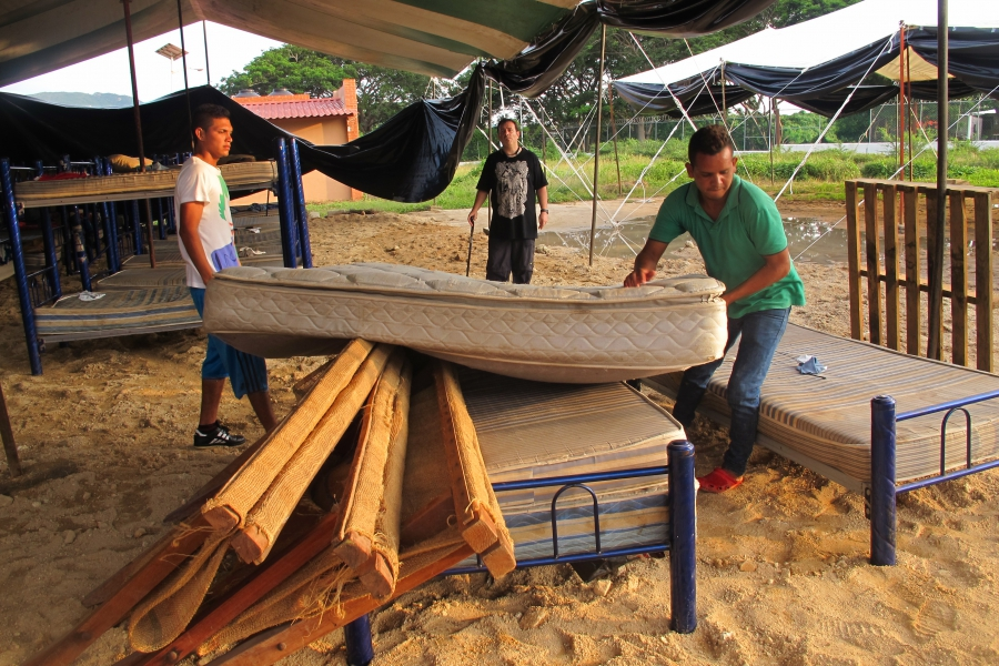 Migrants move beds out of a dormitory badly damaged by the strongest earthquake to hit Mexico in a century into a large tent at the shelter in Ixtepec, Oaxaca.