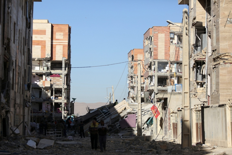 Two men walk in the middle of a street with buildings on either side damaged.