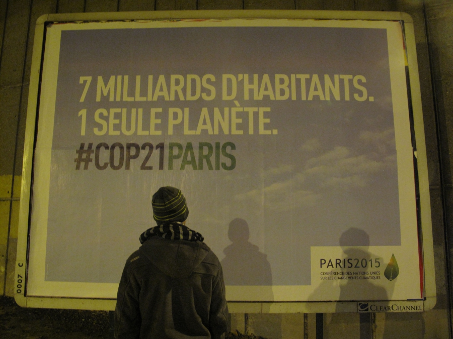 "Joel Domenjoud stands in front of a billboard near his Paris home heralding the climate conference. It says: ""7 billion inhabitants. 1 single planet."" Domenjoud is one of at least 24 climate activists placed under curfew for the duration of the conference"