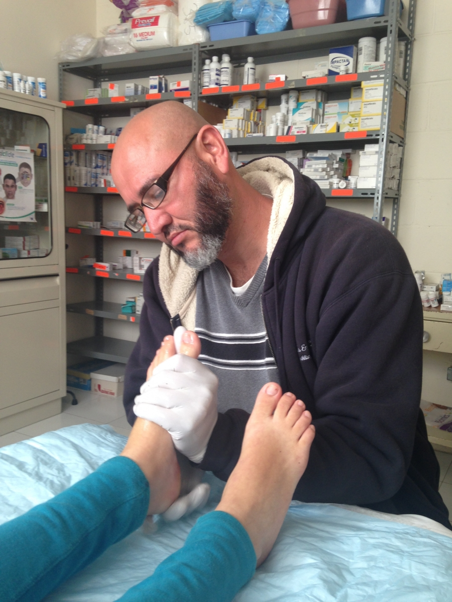 Jorge Gutierrez massages the feet of a woman at a small clinic in Ciudad Juárez, Mexico. She illegally crossed the US border and spent three nights walking through the desert. She was deported by the Border Patrol and sent back to Mexico.