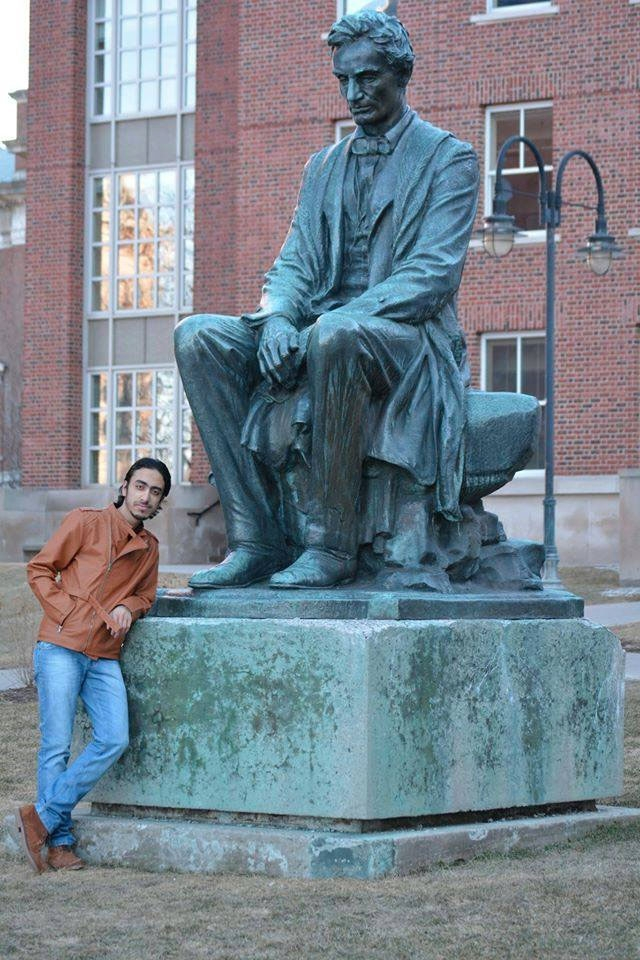 Karam Al Hamad posing with a statue of Abraham Lincoln at Syracuse University.