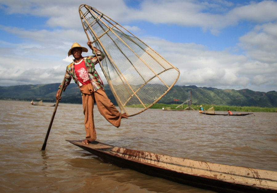 One of Inle Lake's traditional fisherment perches on the prow of his canoe.