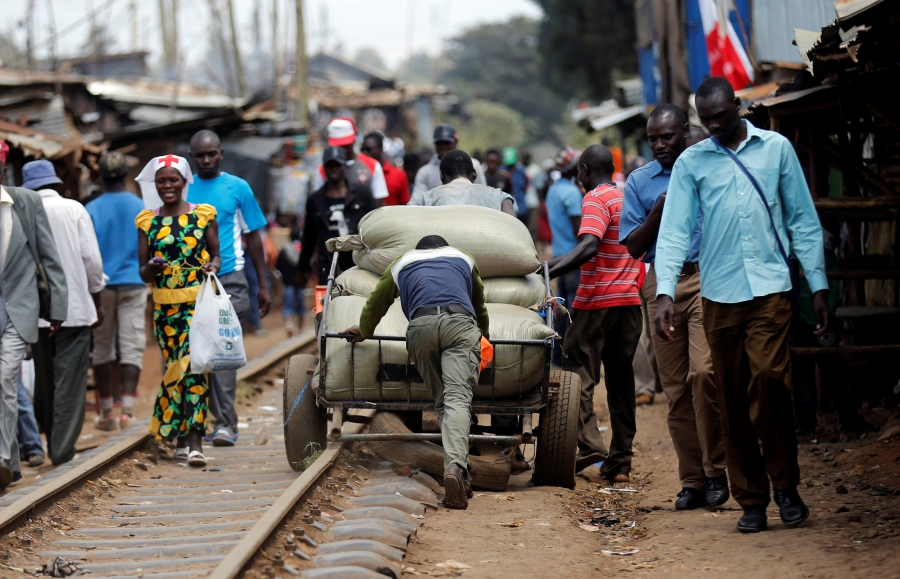 People push a hand cart loaded with maize sacks along the railway line ahead of the presidential election in Kibera slums of Nairobi, Kenya.
