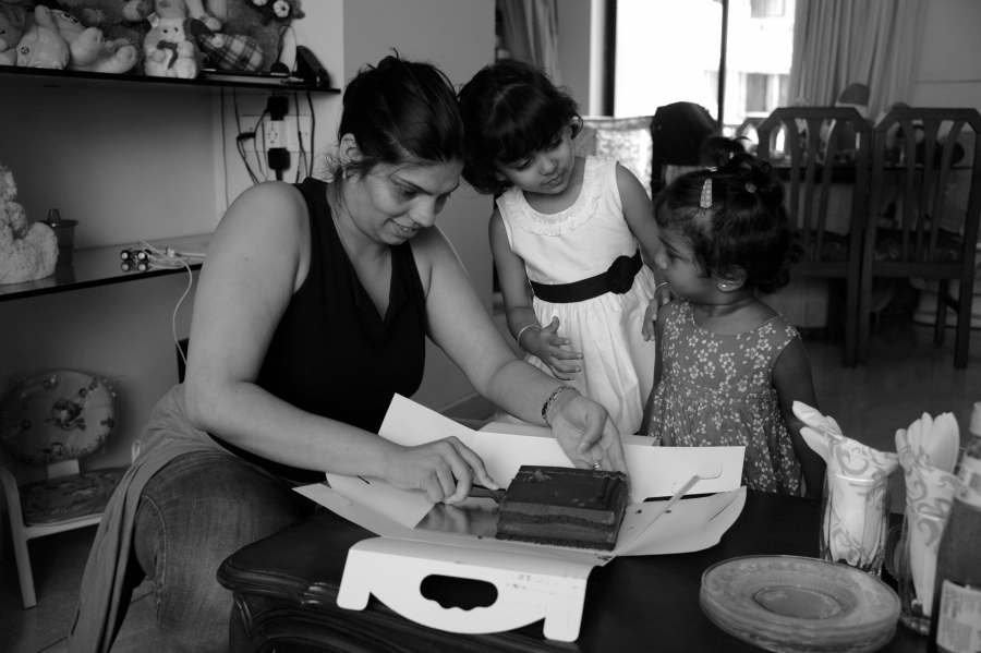 Ayesha D'Souza cuts some chocolate cake for her daughter and five-year-old friend Aliesha, also adopted.