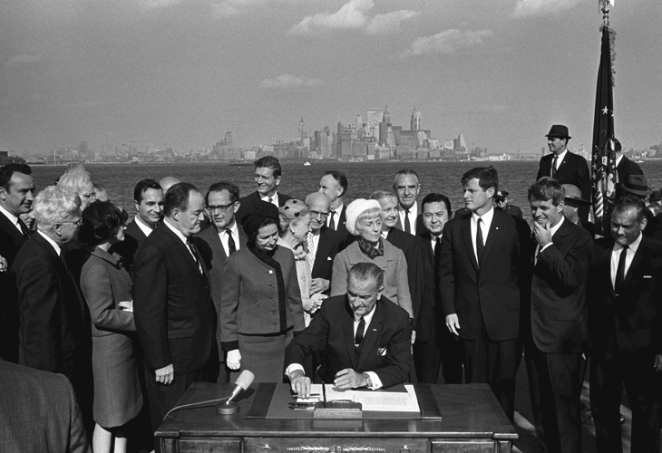 President Lyndon B. Johnson sits at a table and signs the Immigration and Nationality Act on Liberty Island. Vice President Hubert Humphrey, Lady Bird Johnson, Muriel Humphrey, Sen. Edward (Ted) Kennedy, Sen. Robert F. Kennedy, and others look on.