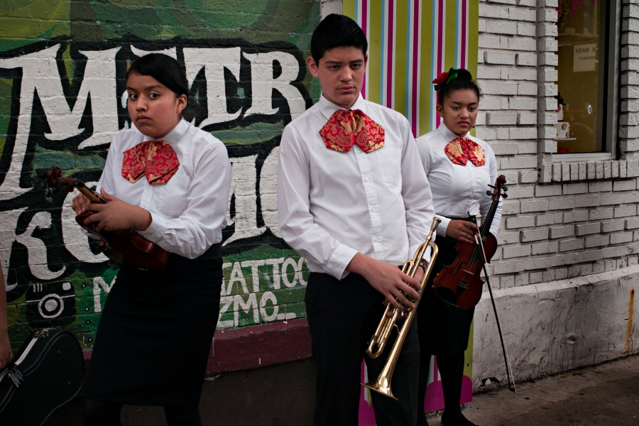 Young people in mariachi clothes with instruments