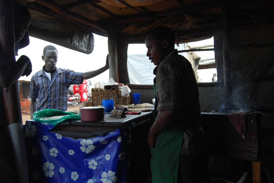 A man sells chapati bread mixed with beans and other local dishes near Bidi Bidi's main entrance area.