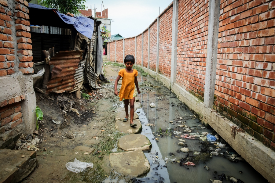 A child walks through the road, which has no drainage facility and all wastes from hanging toilet go directly to the road