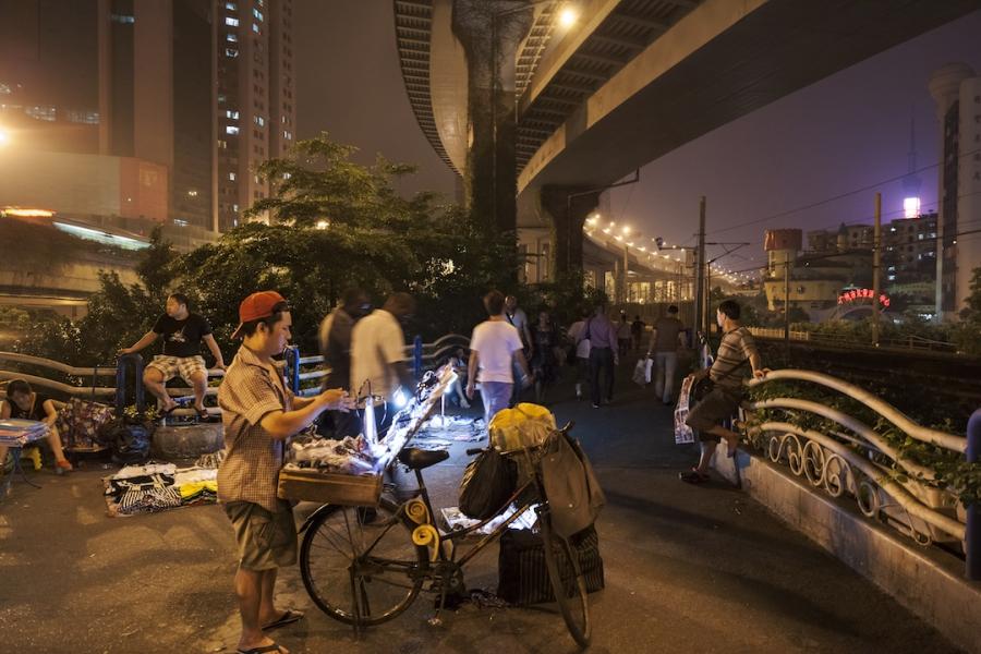 Man selling goods at night market, May 7, 2012