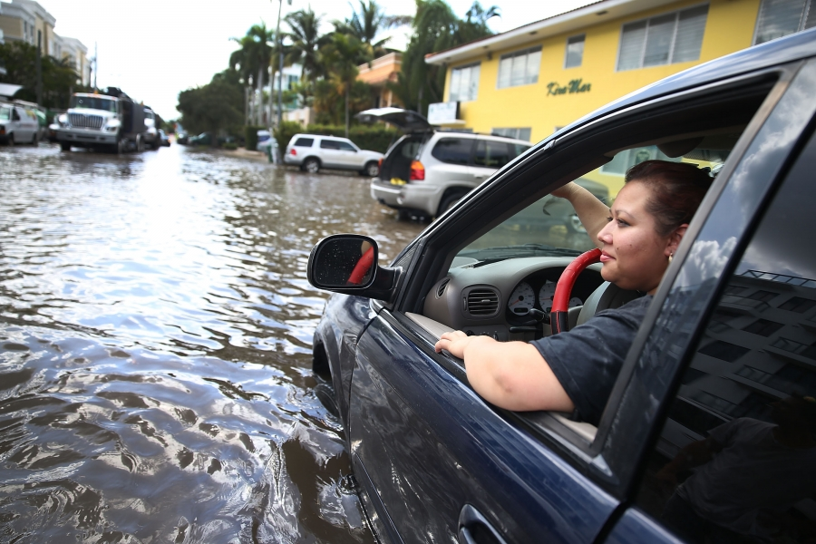 Woman in car on flooded street