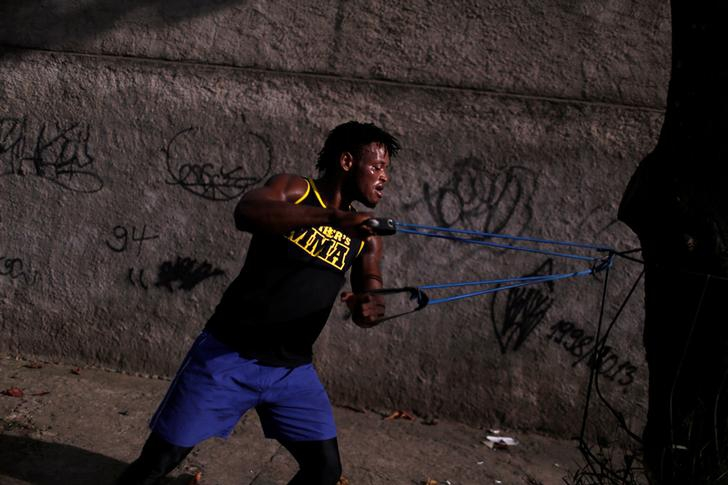 Popole Misenga, a judoka who will compete with a team of refugees during the 2016 olympics, trains with an elastic belt tied to a tree in front of a graffiti covered wall in Rio de Janeiro