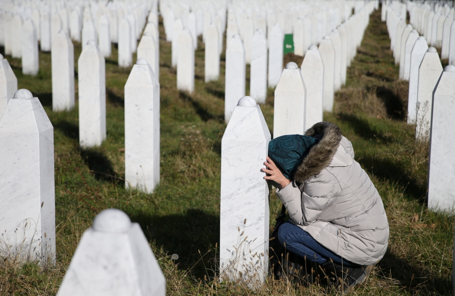 A women kneels with her head down next to a grave marker near Srebrenica.