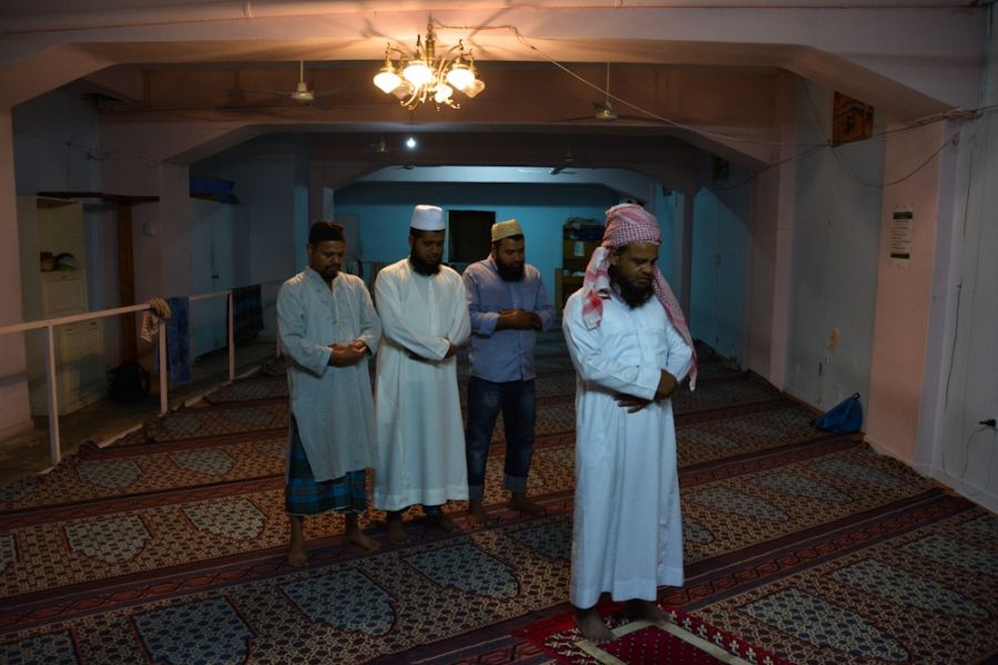 Men from Bangladesh pray on a Friday afternoon at the Hazrat e Umar prayer room in the neighborhood of Kato Patisia, Athens.
