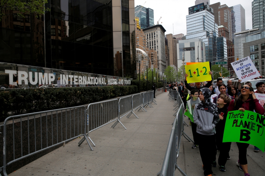 People walk past Trump International Hotel and Tower during the Earth Day 'March For Science NYC' demonstration to coincide with similar marches globally in New York City, April 22, 2017.