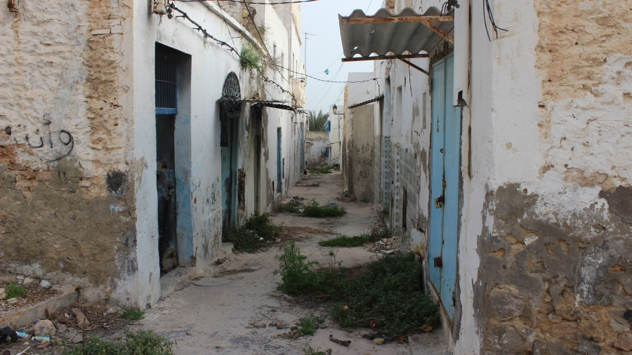 """In Sousse's old town, the former red light district stands derelict and abandoned. Patches of wild grass have lodged in the midst of trash and rubble. """"Go away,"""" reads the graffiti in Arabic painted on the walls."""